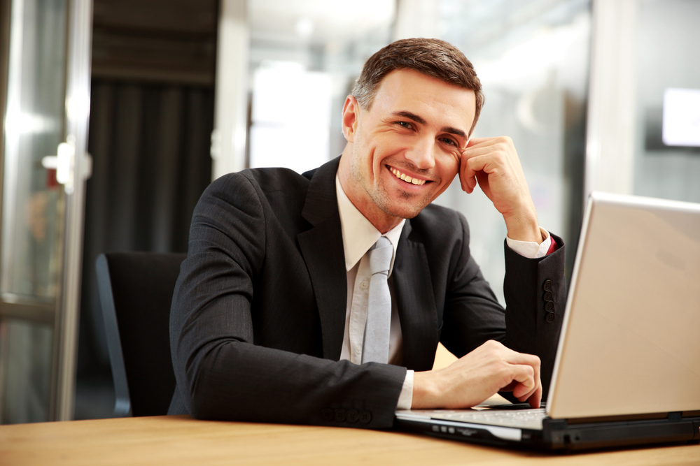 Smiling businessman sitting with laptop at office